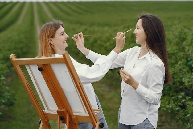 Ragazze eleganti e belle che dipingono in un campo