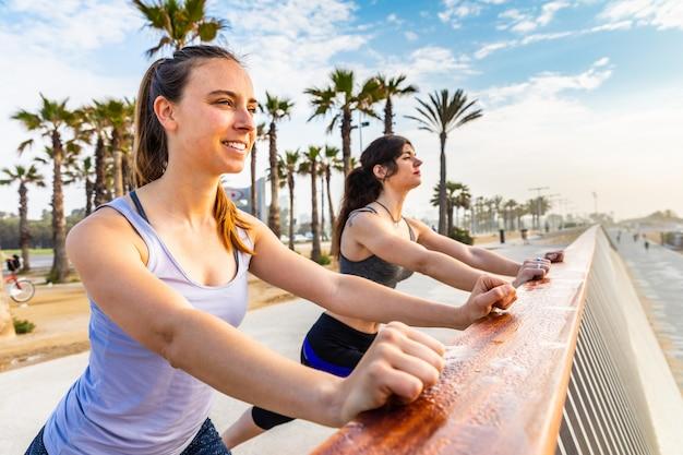 Ragazze facendo esercizi di fitness in riva al mare a barcellona