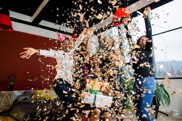 Ragazze felici degli amici dell'afroamericano sotto i coriandoli di caduta alla festa di compleanno