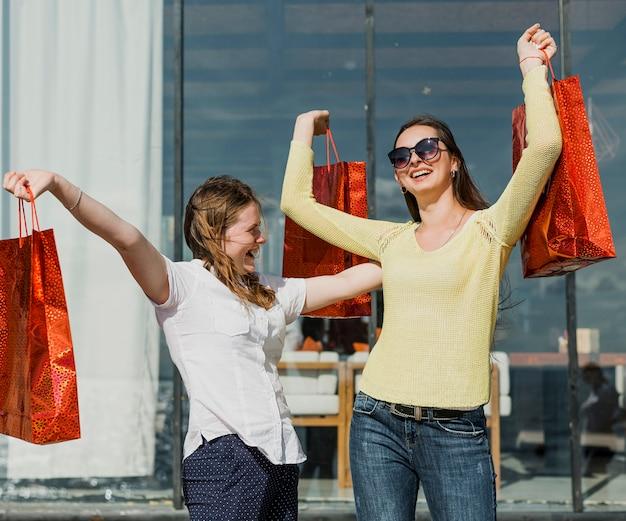 Ragazze felici del colpo medio con i sacchetti della spesa rossi