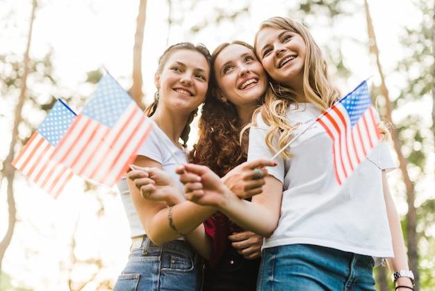 Ragazze felici in natura con bandiere americane