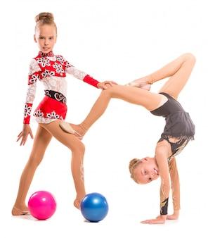 Ragazze flessibili dei gemelli che fanno esercitazione con le sfere.