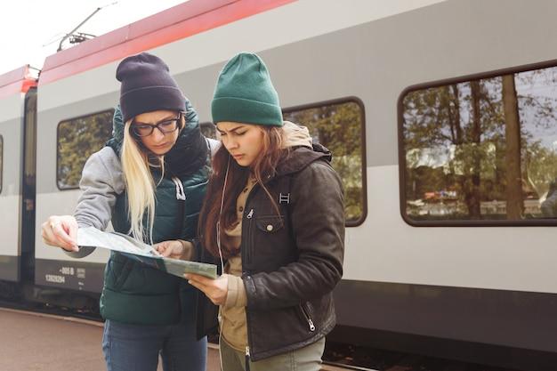 Ragazze giovani hipster con zaino e mappa aspettano il treno.