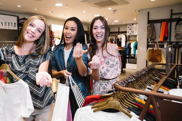 Ragazze graziose che propongono alla fotocamera in negozio