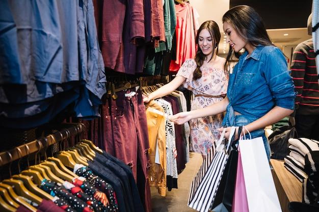 Ragazze graziose scegliendo vestiti in negozio