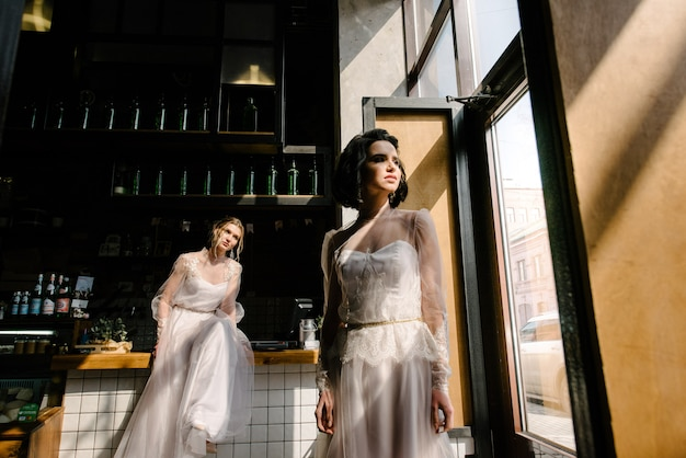 Ragazze in abiti da sposa bianchi stanno posando.