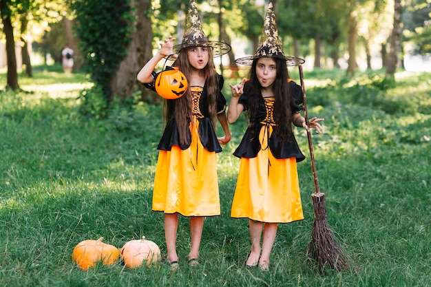 Ragazze in costumi strega facendo facce tenendo la scopa e la zucca