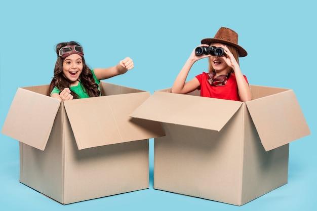 Ragazze in scatole di cartone animato che giocano a esploratori