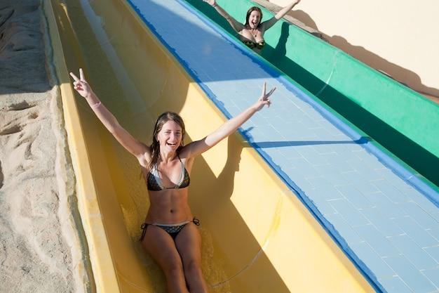 Ragazze in scivolo acquatico piscina presso aquapark