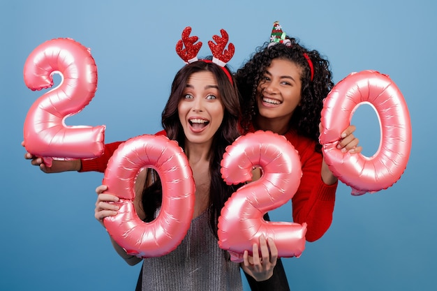Ragazze multirazziali felici con i palloni da 2020 nuovi anni e cerchi divertenti di festa isolati sopra il blu