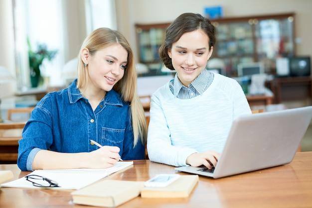 Ragazze positive che lavorano alla ricerca in biblioteca