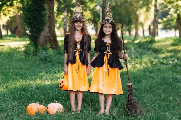 Ragazze ridenti in costumi strega che si tengono per mano, scopa e zucca