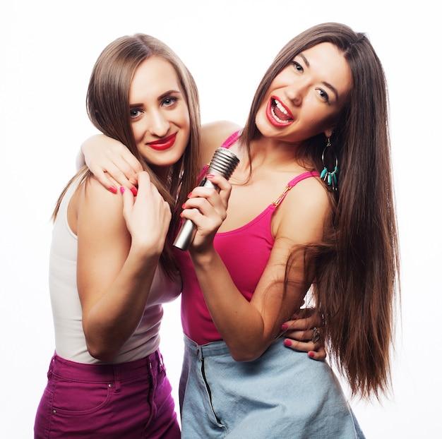 Ragazze sensuali che cantano con il microfono