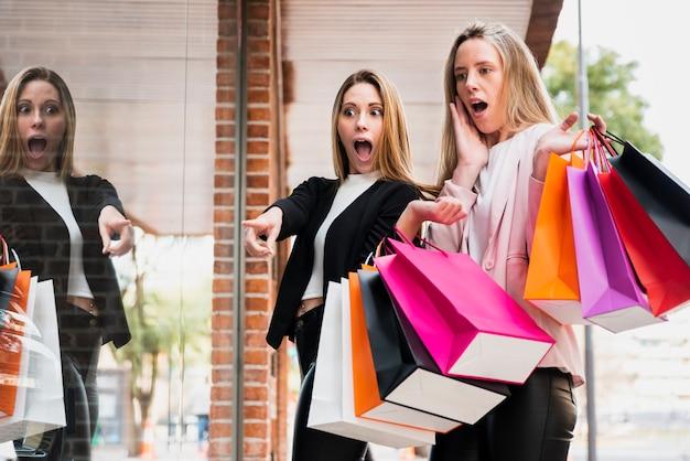 Ragazze sorprese con i sacchetti della spesa che esaminano finestra