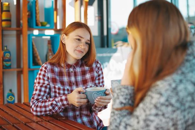 Ragazze sorridenti che bevono caffè
