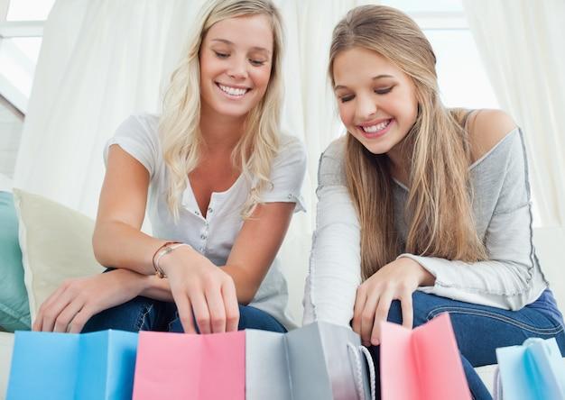 Ragazze sorridenti che guardano le borse sotto di loro