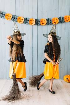 Ragazze sorridenti in abiti da strega in possesso di manici di scopa