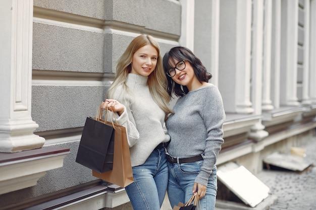 Ragazze sveglie con il sacchetto della spesa in una città