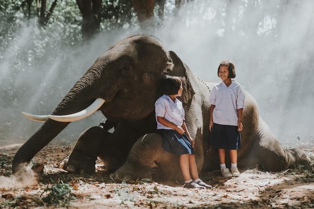 Ragazze tailandesi che giocano dopo la scuola nella giungla vicino al loro amico elefante