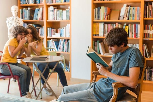 Ragazze teenager che spettegolano sulla lettura del compagno di classe