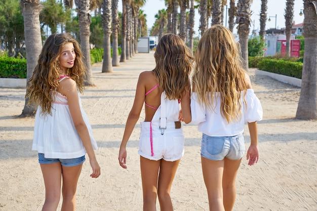 Ragazze teenager dei migliori amici che camminano nelle palme