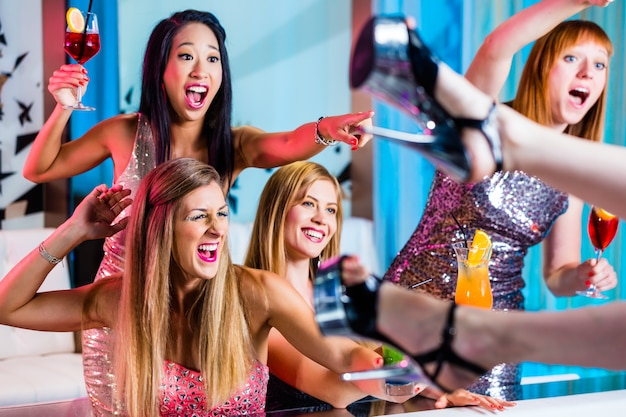 Ragazze ubriache con cocktail fantasiosi in strip club