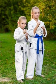 Ragazze vestite kimono facendo esercizi di karate