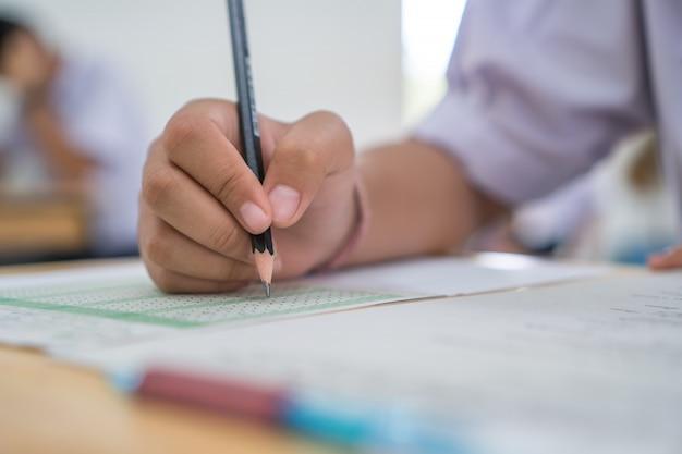 Ragazzi asiatici studenti che partecipano agli esami, scrivendo a una camera d'esame con studenti universitari