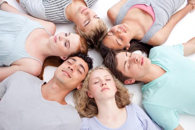 Ragazzi che dormono sul pavimento con le teste insieme