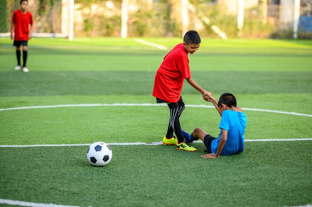 Ragazzi che giocano a calcio sul campo di pratica del calcio