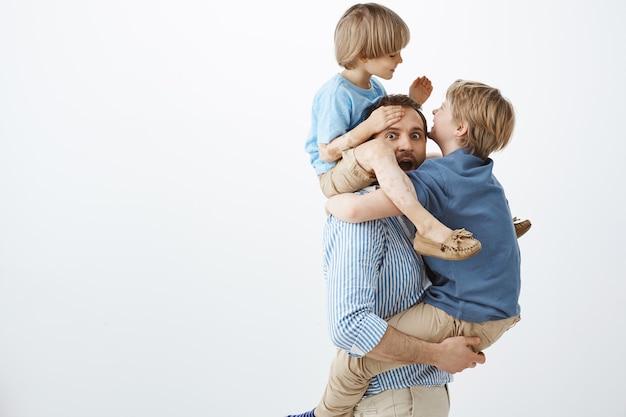 Ragazzi che scherzano con un bel papà. ritratto di figli felici giocosi che appendono sul corpo del padre, divertirsi e giocare insieme