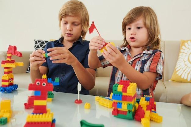 Ragazzi creativi che giocano con i mattoni di plastica