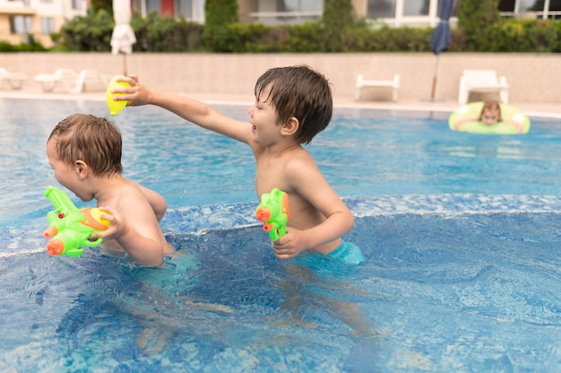 Ragazzi di vista laterale che giocano in piscina