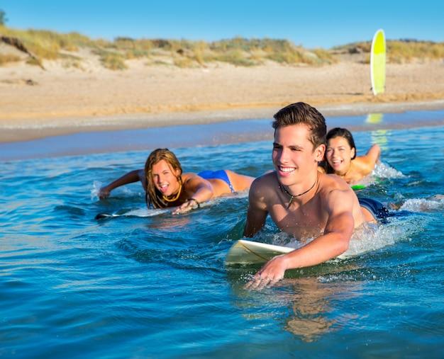 Ragazzi e ragazze del surfista dell'adolescente che nuotano sopra il surf