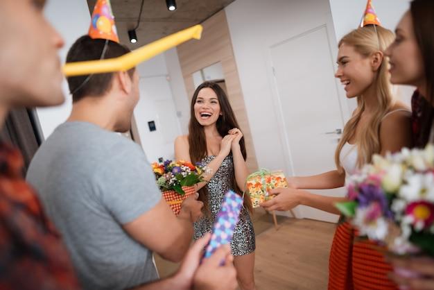 Ragazzi e ragazze incontrano la ragazza del compleanno con i regali