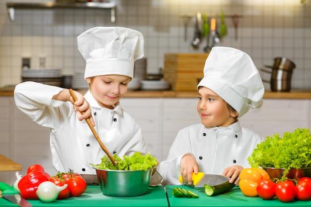Ragazzi felici divertenti che cucinano alla cucina del ristorante