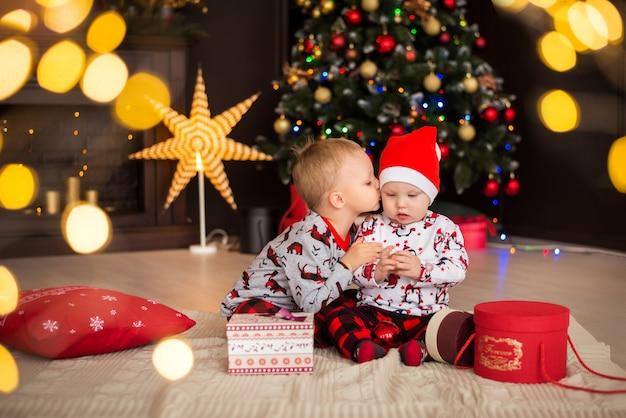Ragazzi, fratelli, bambini in costumi natalizi, pigiami con decorazioni natalizie
