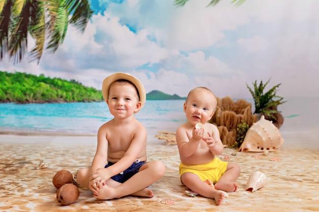 Ragazzi, fratelli prendono il sole su una spiaggia sabbiosa con palme in riva al mare, giocano con noci di cocco e conchiglie
