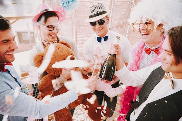 Ragazzi gay che aprono e bevono champagne alla festa.