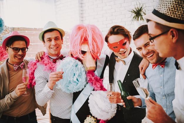 Ragazzi gay in posa con bicchieri di champagne alla festa