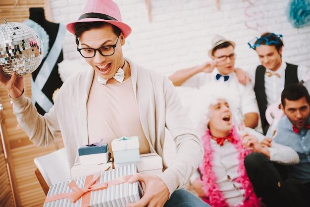 Ragazzi gay rapiti in cravatte a farfalla aprono regali alla festa.