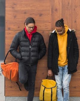 Ragazzi medio lunghi in piedi con le borse