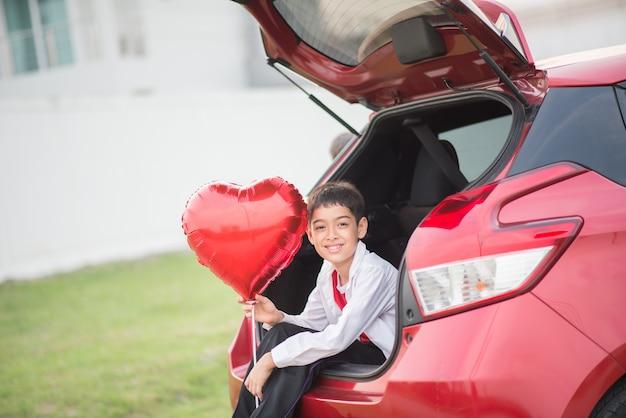 Ragazzini seduti sulla porta posteriore dell'auto con palloncino cuore in mano