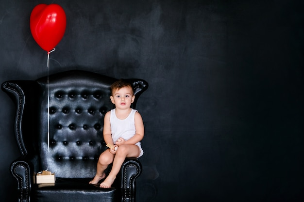 Ragazzino 2 anni nella maglietta bianca che si siede sulla poltrona con palloncino cuore rosso