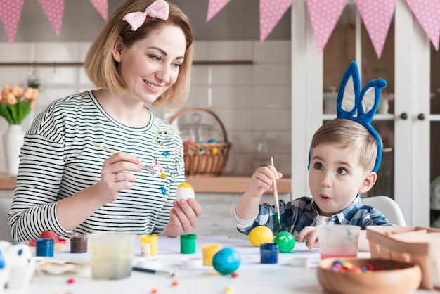 Ragazzino adorabile che dipinge le uova di pasqua con la madre