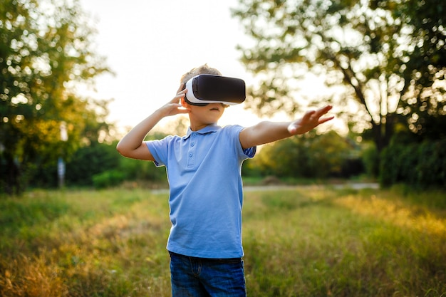 Ragazzino affascinato che utilizza gli occhiali per realtà virtuale vr. all'aperto
