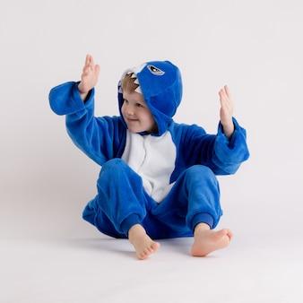 Ragazzino allegro che posa su un fondo bianco in pigiama, costume dello squalo blu