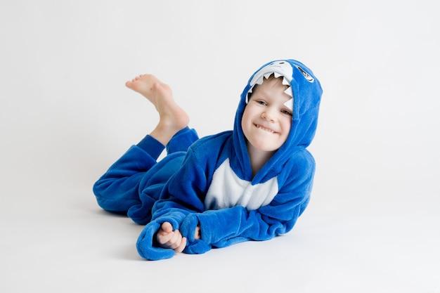 Ragazzino allegro che propone su una priorità bassa bianca in pigiama, costume dello squalo blu