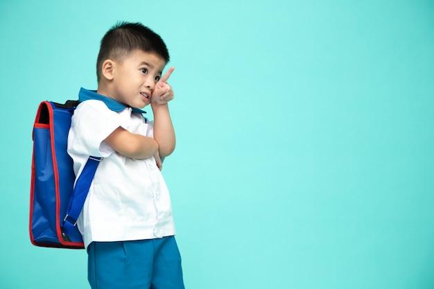 Ragazzino asiatico sorridente allegro in un'uniforme scolastica con lo zaino che indica su sullo spazio della copia isolato sulla parete verde, sul primo giorno dell'asilo e sul concetto di istruzione di ritorno a scuola