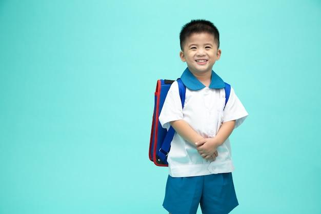Ragazzino asiatico sorridente allegro in un'uniforme scolastica con lo zaino divertendosi isolato sulla parete verde, sul primo giorno dell'asilo e sul concetto di ritorno a scuola